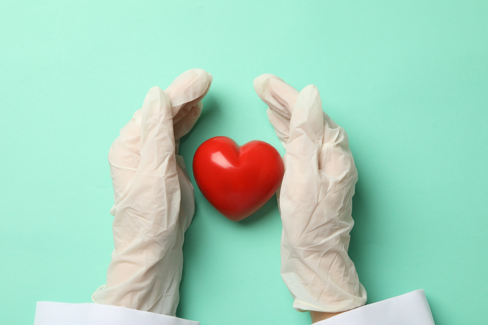 Female doctor hands in gloves and heart on mint background